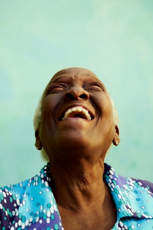 Old people and emotions, portrait of bizarre senior african american lady laughing with head tilted up photo