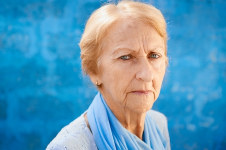Senior people portrait, happy sad blonde woman in blu clothes looking at camera against blue wall photo
