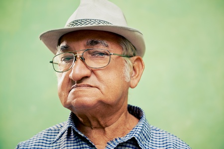 people and emotions, portrait of serious senior hispanic man with glasses and hat looking at camera against green background photo