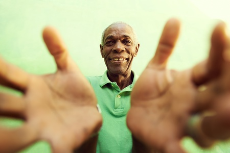 african people: portrait of senior black man with hands and arms open pointing at camera. Green background