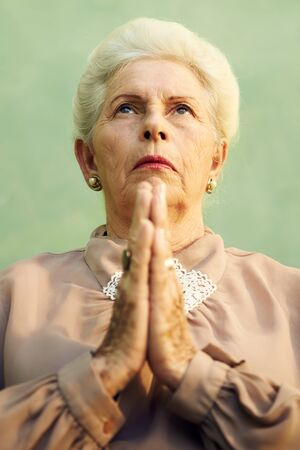 one senior woman only: Elderly women and religion, portrait of serious senior caucasian woman with hands joined praying god on green background Stock Photo