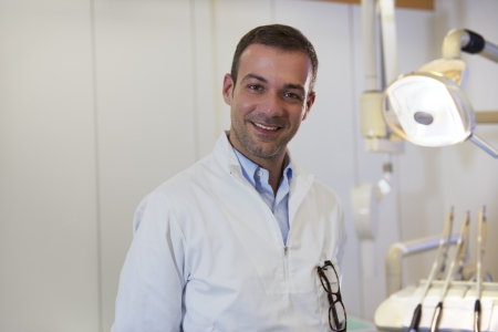 Dental care and hygiene, portrait of adult caucasian dentist at work and smiling at camera photo