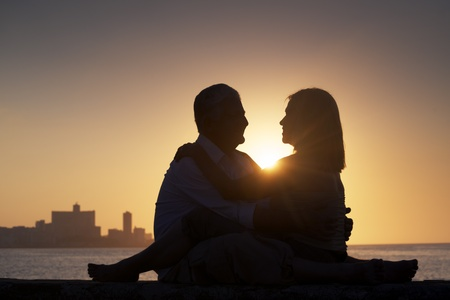 Elderly couple in love, honeymoon with old man and woman kissing near the sea at sunset in La Habana, Cuba. Silhouette of couple and skyline of the city photo
