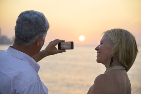 Travel and active elderly man and woman, couple of tourists looking at sea and taking picture with smartphone
