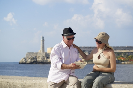 guide book: Tourism and active retirement with elderly people traveling, senior couple having fun on holidays in Havana, Cuba