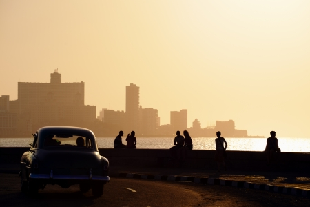 habana: Skyline in La Habana, Cuba, at sunset, with vintage cars on the street and people sitting on the Malecon. Copy space Stock Photo