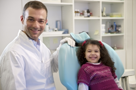 Doctor during visit of female child in dental clinic, portrait of young baby girl looking at camera and smiling photo