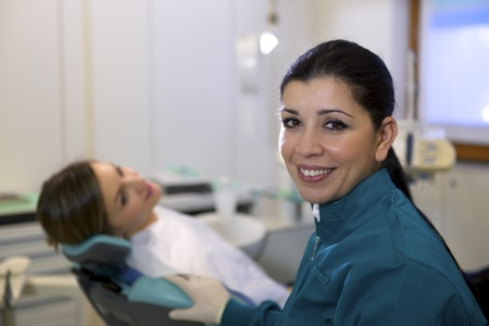 Doctor during visit of woman in dental clinic, portrait of female dentist looking at camera and smiling Stock Photo - 19357244