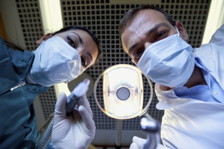 dentist mask: Medical personnel and staff at work in dental clinic, dentist and assistant working with customer. Low angle