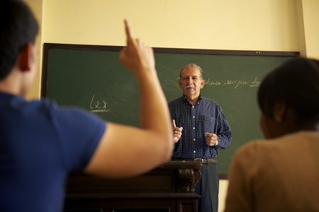 People at school, student raising hand and asking question to professor during class in college, Law School, University of Havana, Cuba photo