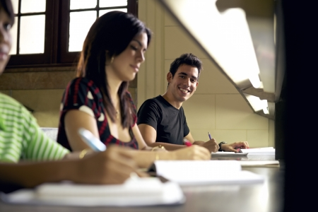 school exam: Happy student studying and writing, portrait of hispanic young man doing homework in college library and smiling at camera Stock Photo