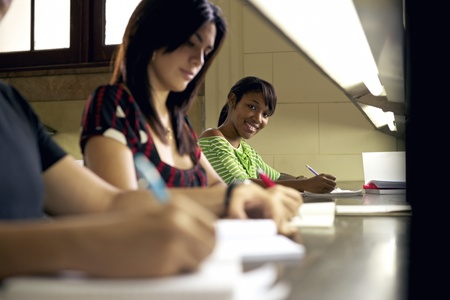 Portrait of happy female student writing and preparing test, pretty black girl smiling at camera in college library photo