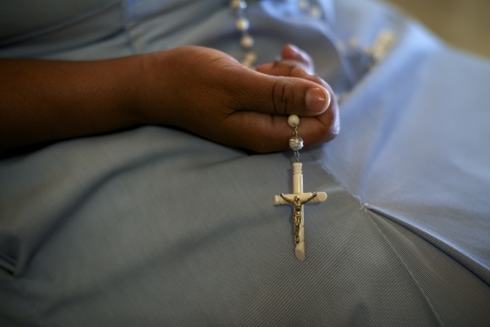 catholic mass: People and religion, catholic sister praying in church and holding cross in hands. With model release Stock Photo