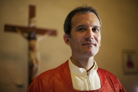 people in church: portrait of catholic priest on altar in church