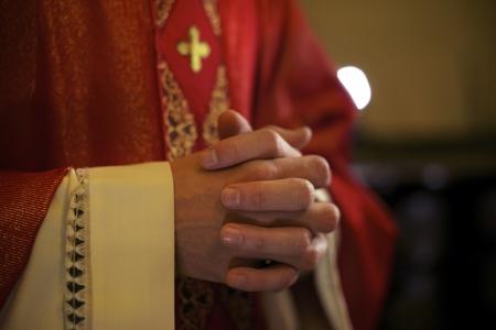 Sacerdote católico en el altar orando con las manos juntas en misa en la iglesia