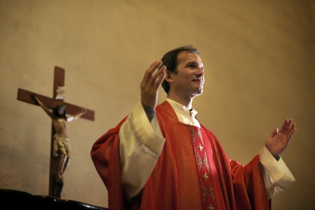 Catholic priest on altar praying with open arms during mass service in church photo
