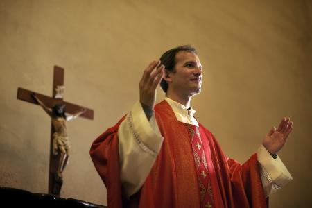 Sacerdote católico en el altar rezando con los brazos abiertos durante la misa en la iglesia