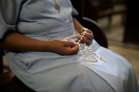 Les gens et la religion, soeur catholique priant dans l'église et la tenue de croix dans les mains. Avec le modèle libération Banque d'images