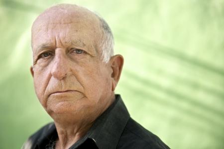 Ouderen en emoties, portret van ernstige senior blanke man kijken camera tegen groene muur