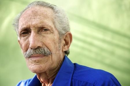 Les personnes âgées et les émotions, portrait d'homme sérieux caucasien aîné regardant la caméra contre un mur vert
