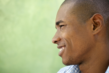 Portrait of happy young african american man looking away and smiling. Head and shoulders, copy space photo
