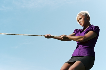 resolute: resolute business woman pulling rope against blue sky