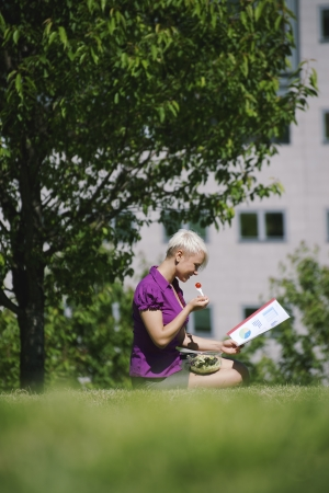 young business woman sitting on grass in park, eating salad for lunch and reading paperwork  photo