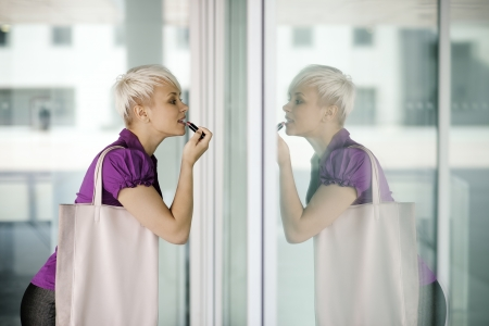 business woman in a hurry applying make up outdoor and looking at office building window photo