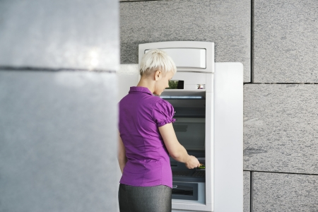 withdrawing: business woman withdrawing cash at bank atm machine