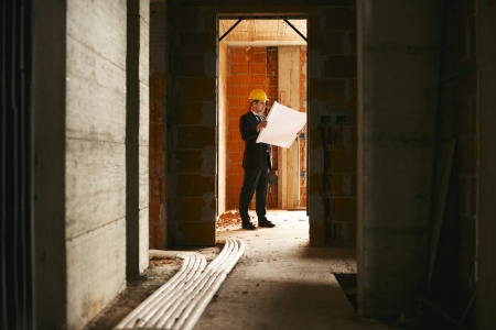 Engineer at work in construction site, standing in apartment building and looking at blueprints and plans photo