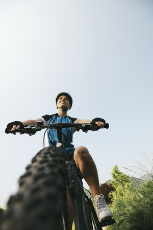 young woman training on mountain bike and cycling in park. Copy space, low angle view photo