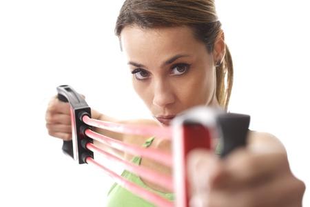mediados de mujer adulta que hace ejercicio f�sico y los m�sculos de entrenamiento con la goma en el fondo blanco photo