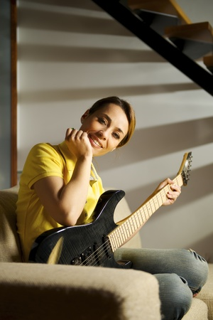 portrait of beautiful mid adult woman playing electric guitar at home, sitting on sofa photo