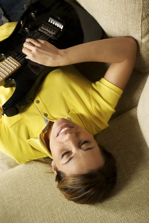 beautiful mid adult woman playing electric guitar at home, laying on sofa photo