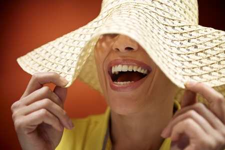 mid adult woman with straw hat smiling and having fun on red background photo