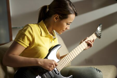 beautiful mid adult woman playing electric guitar at home, sitting on sofa photo