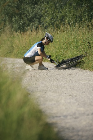 puncture: young woman training on mountain bike and repairing flat tyre on track in countryside Stock Photo