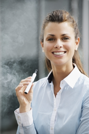 a smoke: portrait of young female smoker smoking e-cigarette outdoor office building and looking at camera