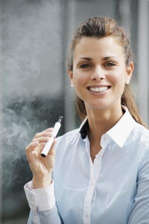 portret van jonge vrouwelijke roker roken e-sigaret buiten kantoor gebouw en kijken naar de camera Stockfoto