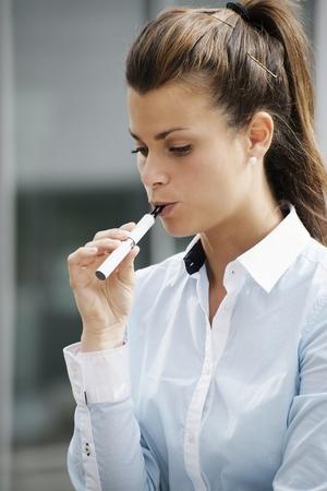 mujeres jóvenes fumadores de fumar e-cigarrillo al aire libre. La cabeza y los hombros, vista lateral Foto de archivo
