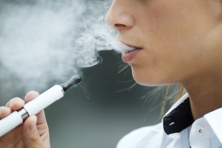primer plano de la mujer que fuma e-cigarrillo y el humo que goza. Copie el espacio