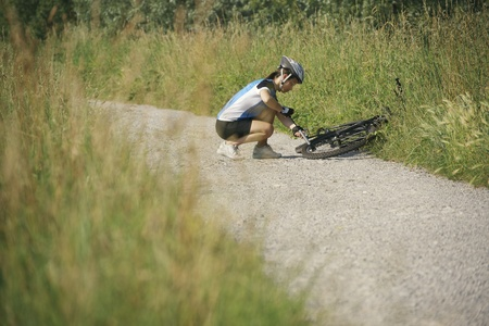 flat tire: young woman training on mountain bike and repairing flat tyre on track in countryside Stock Photo