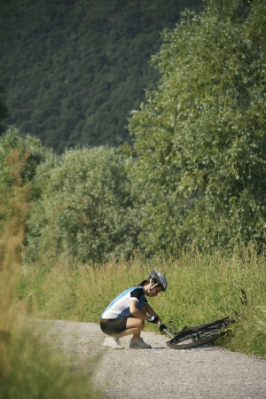 flat tyre: young woman training on mountain bike and repairing flat tyre on track in countryside Stock Photo