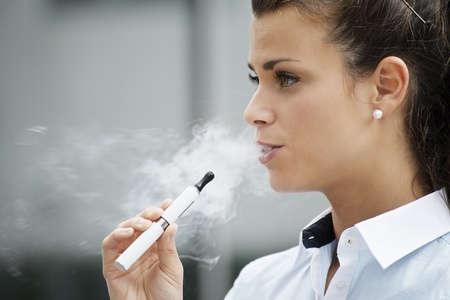quit: young female smoker smoking e-cigarette outdoors. Head and shoulders, side view