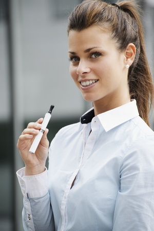 substitution: portrait of young female smoker smoking e-cigarette outdoor office building and looking at camera