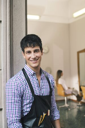 portrait of young male hairstylist standing out of shop and looking at camera  Stock Photo - 21269952