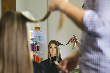 woman looking at mirron and cutting hair in hairdresser shop Stock Photo - 21307390