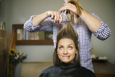 beauty saloon: female client in hairdresser shop uncertain about cutting hair and biting lips