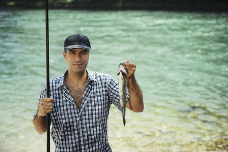 fisher: mid adult fisherman on holidays on river, relaxing and fishing trout. Copy space Stock Photo