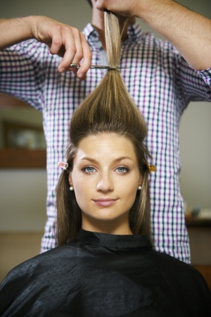 hair stylist: female client in hairdresser shop happy about cutting long hair and looking at camera